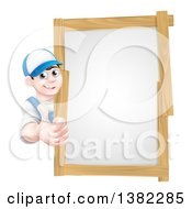 Clipart Of A Happy Young Brunette Caucasian Mechanic Man In Blue Wearing A Baseball Cap Giving A Thumb Up Around A Wood Framed Sign Royalty Free Vector Illustration