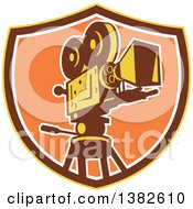 Clipart Of A Retro Film Movie Camera In A Yellow Brown And Orange Shield Royalty Free Vector Illustration by patrimonio