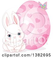 Cute White Easter Bunny Rabbit Sitting By A Giant Easter Egg With Hearts
