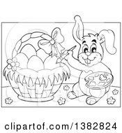 Clipart Of A Black And White Lineart Happy Easter Bunny Rabbit Painting Eggs In A Basket Royalty Free Vector Illustration