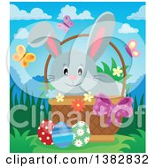 Clipart Of A Happy Gray Easter Bunny Rabbit In A Basket Of Eggs With Spring Flowers And Butterflies On A Sunny Day Royalty Free Vector Illustration