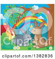 Clipart Of Happy Brown And Gray Bunny Rabbits In A Yard Royalty Free Vector Illustration