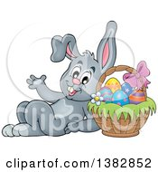 Clipart Of A Happy Gray Easter Bunny Rabbit Leaning Against A Basket Of Eggs Royalty Free Vector Illustration