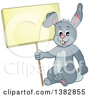 Clipart Of A Happy Gray Bunny Rabbit Holding A Blank Sign Royalty Free Vector Illustration