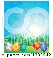 Clipart Of A Background Of Patterned Easter Eggs Grass And Flowers Against A Blue Sky With Sunshine Royalty Free Vector Illustration by visekart