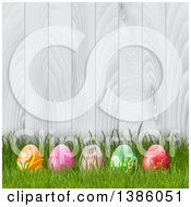 Clipart Of 3d Easter Eggs In Grass Against A White Wood Fence Royalty Free Vector Illustration