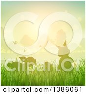 Clipart Of Silhouetted Bunny Rabbits With Butterflies And An Egg In Grass Against A Sunset Royalty Free Vector Illustration