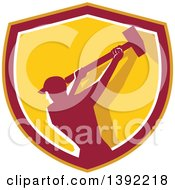 Clipart Of A Retro Silhouetted Male Demolition Worker Swinging A Sledgehammer In A Yellow Red And White Shield Royalty Free Vector Illustration