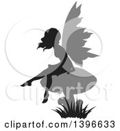 Clipart Of A Black Silhouetted Female Fairy With Gray Wings Sitting On A Mushroom Royalty Free Vector Illustration