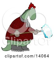 Green Dino In A Coat And Hat Shoveling Snow In Winter