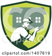 Clipart Of A Retro Male Mover Carrying A House In A Green Shield Royalty Free Vector Illustration
