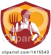Clipart Of A Retro Male Farmer Or Worker Standing With One Hand In His Pocket And One Hand Holding A Pitchfork In A Red And Orange Shield Royalty Free Vector Illustration