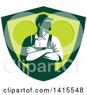 Clipart Of A Retro Male Farmer With Folded Arms Looking To The Side In A Green Shield Royalty Free Vector Illustration