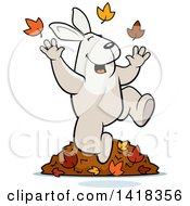 Cartoon Clipart Of A Happy Rabbit Playing In Autumn Leaves Royalty Free Vector Illustration