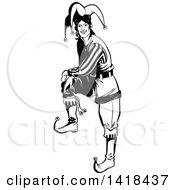 Clipart Of A Black And White Jester Joker Resting A Foot On An Invisible Object Royalty Free Vector Illustration by Frisko