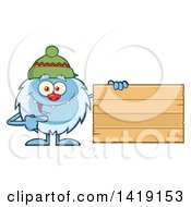 Cartoon Yeti Abominable Snowman Wearing A Winter Hat And Pointing To A Blank Wood Sign