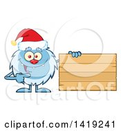 Cartoon Yeti Abominable Snowman Wearing A Christmas Santa Hat And Pointing To A Blank Wood Sign