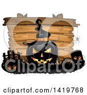 Black Halloween Jackolantern Pumpkin Wearing A Witch Hat In A Cemetery Over A Wood Sign