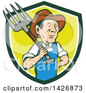Clipart Of A Retro Cartoon Male Farmer Or Worker Holding A Pitchfork Over His Shoulder Emerging From A Green White And Yellow Shield Royalty Free Vector Illustration