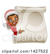 Clipart Of A Happy Black Female Christmas Elf Pointing Around A Blank Scroll Sign Royalty Free Vector Illustration by AtStockIllustration