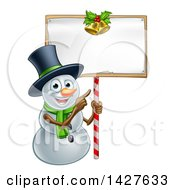 Clipart Of A Happy Christmas Snowman Wearing A Top Hat And Pointing To A Blank Sign Royalty Free Vector Illustration by AtStockIllustration