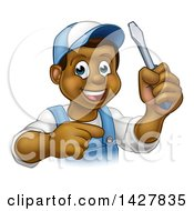 Clipart Of A Cartoon Happy Black Male Electrician Holding Up A Screwdriver And Pointing Royalty Free Vector Illustration by AtStockIllustration