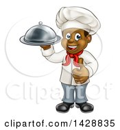 Clipart Of A Happy Young Black Male Chef Holding A Cloche Platter And Giving A Thumb Up Royalty Free Vector Illustration