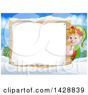 Clipart Of A Happy Caucasian Male Christmas Elf Giving A Thumb Up Around A Blank Sign In A Winter Landscape Royalty Free Vector Illustration by AtStockIllustration
