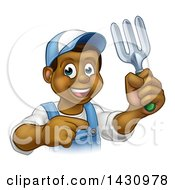 Clipart Of A Cartoon Happy Black Male Gardener In Blue Holding A Garden Fork And Pointing Royalty Free Vector Illustration