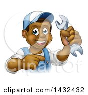 Cartoon Happy Black Male Mechanic Holding Up A Wrench And Pointing