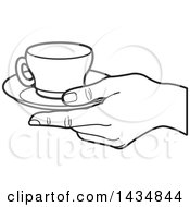 Black And White Hand Holding A Tea Cup And Saucer
