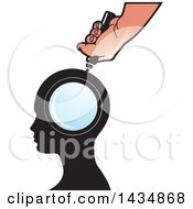Hand Holding A Magnifying Glass Over A Silhouetted Head