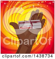 Hand Holding Out A Small Christmas Gift Box Over A Yellow And Red Swirl With Sparkles And Stars