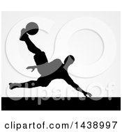 Clipart Of A Black Silhouetted Male Soccer Player Kicking Over Gray Royalty Free Vector Illustration by AtStockIllustration