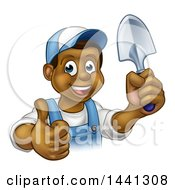 Clipart Of A Cartoon Happy Black Male Gardener In Blue Holding A Garden Trowel And Giving A Thumb Up Royalty Free Vector Illustration
