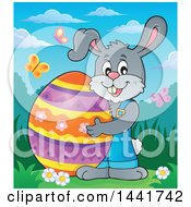 Happy Gray Easter Bunny Rabbit Holding A Giant Egg In A Spring Landscape