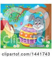 Happy Gray Easter Bunny Rabbit Holding A Giant Egg By A Tree