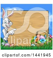 Cartoon Happy White Easter Bunny Rabbit Pointing Around A Wood Sign With A Basket And Eggs Against Sky