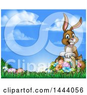 Happy Brown Easter Bunny With A Basket Of Eggs And Flowers In The Grass Against A Blue Sky