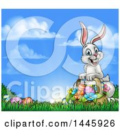 Happy Easter Bunny With A Basket Of Eggs And Flowers In The Grass Against A Blue Sky
