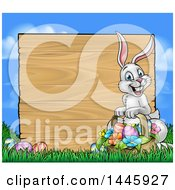 Happy Easter Bunny With A Basket Of Eggs And Flowers In The Grass With A Blank Wood Sign Against A Blue Sky