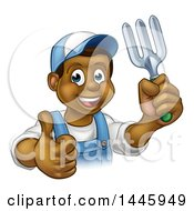 Clipart Of A Cartoon Happy Black Male Gardener In Blue Holding Up A Thumb A Garden Fork Royalty Free Vector Illustration