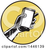 Clipart Of A Retro Woodcut Hand Holding A Smart Phone In A Yellow And Black Circle Royalty Free Vector Illustration by patrimonio