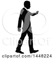 Clipart Of A Black And White Silhouetted Business Man Walking And Checking His Watch Royalty Free Vector Illustration