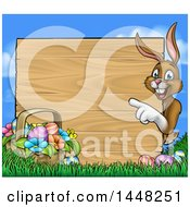 Cartoon Happy Brown Easter Bunny Rabbit Pointing Around A Wood Sign With A Basket And Eggs In Grass