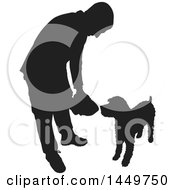 Clipart Graphic Of A Black And White Silhouetted Man Feeding His Dog Royalty Free Vector Illustration