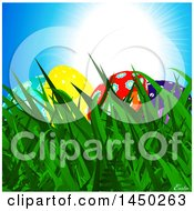 Clipart Graphic Of Colorful Easter Eggs In Grass Under A Blue Sunny Sky Royalty Free Vector Illustration