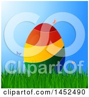 3d Colorful Striped Easter Egg In Grass With Butterflies Over Blue