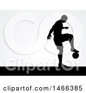 Black Silhouetted Male Soccer Player Kicking Over Gray