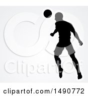 Silhouetted Male Soccer Player Heading A Ball Over Gray